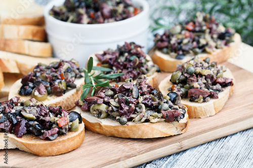 Valokuva  Homemade mixed Olive Tapenade made with garlic, capers, olive oil, Kalamata, black and green olives spread over toasted bread