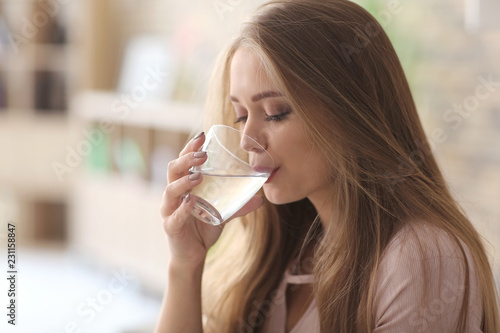 Beautiful young woman drinking water at home