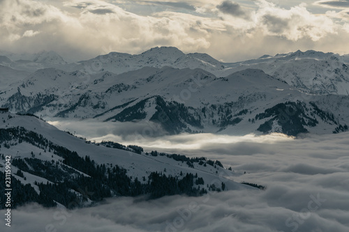 Ski slopes on the hills of Austrian Alps mountains above clouds