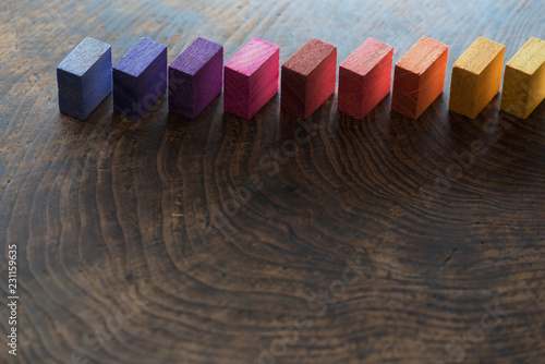 Photo Colored wooden blocks diagonally aligned on a old vintage wooden table