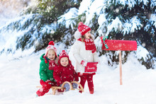 Children With Letter To Santa At Christmas Mail Box In Snow