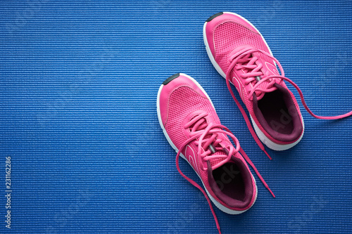 Fotografia  Pair of pink running sneakers for woman on a blue background