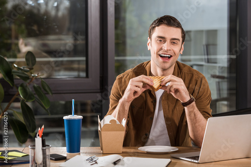Valokuva handsome happy businessman eating sandwich and take away noodles at office