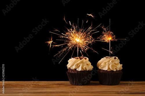 Photo  Tasty chocolate cupcakes with sparkler on wooden table against dark background