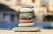 Balance pyramid of spa stones on natural blurred background.