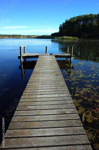Long wooden bridge in lake with calm water and blue sky in Sweden, Scandinavia, Europe. Peaceful outdoor image on Malaren lake in Vastmanland