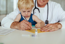 Toddler Sitting On Doctor's Lap, While Filling In Immunization Card