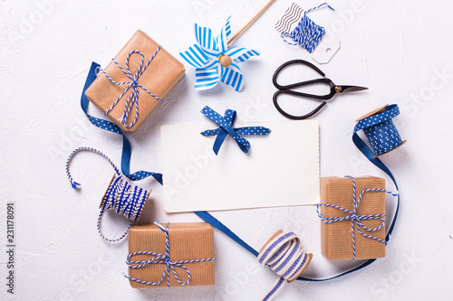 Empty tag and wrapped gift boxes with presents on white textured background.