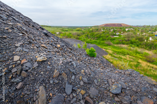 Canvas Print The close-up view of the mine waste heap with the other slagheap and the village at the background