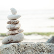 Balanced Zen stones on blurred beach background, concept of balance and harmony