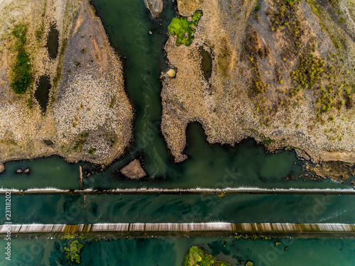 Aerial top view of water dam in with sand bar from 100m