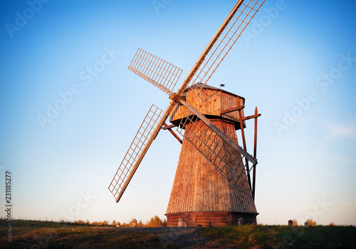 Poster Molens Traditional old wooden windmill in the evening against the cloudless sky.