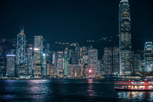 Ferry Passing The Victoria Harbor  At Night  In Hong Kong