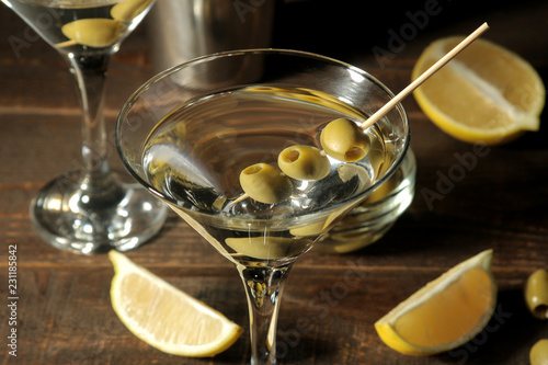 Spoed Fotobehang Aromatische Martini in a glass wineglass with green olives on a skewer on a brown wooden table. cocktails. bar