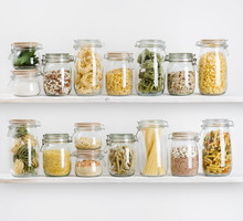 Various Uncooked Groceries In Glass Jars Arranged On Wooden Shelves