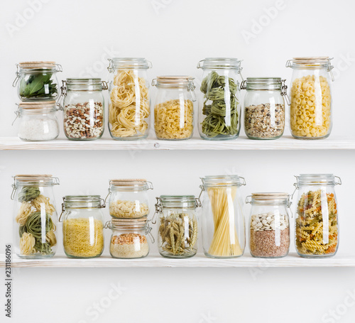 Obraz na płótnie Various uncooked groceries in glass jars arranged on wooden shelves
