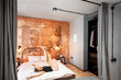 Modern loft bedroom intreior with bright copper wall and motion blurred woman jumping on the bed