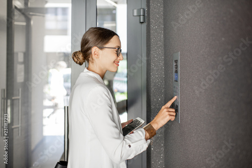 Fotografie, Obraz  Young business woman in white suit entering code on the intercom keyboard of the