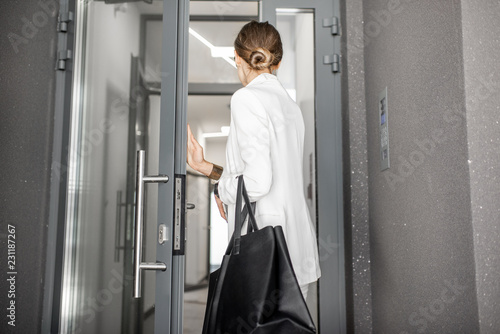 Stampa su Tela Young business woman in white suit entering to the hall of the modern residentia