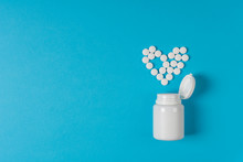 Medicine Pills Heart Shaped On Blue Background. Heart Protection. Drug Prescription For Treatment Medication. Pharmaceutical Medicament, Cure In Container For Health. Top View. Flat Lay.