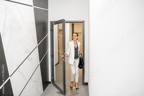 Fotografía  Businesswoman in white suit walking the corridor of the modern residential build
