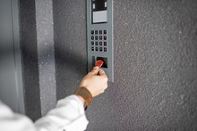 Close-up Of Intercome Keyboard Of Residential Building With Keychain Opening The Door