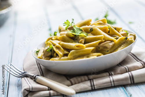 Pasta pene with chicken pieces mushrooms parmesan cheese sauce and herb decor...