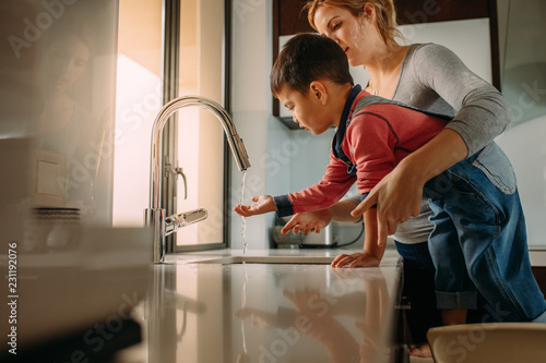 Fotomural  Little boy with mother washing hands in kitchen sink