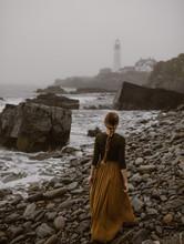 Woman Walking Along A Foggy Co...