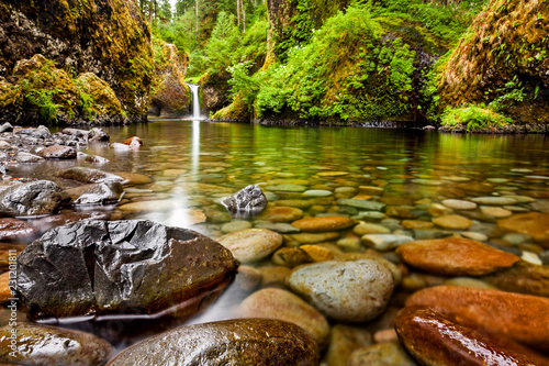 Spoed Foto op Canvas Natuur Punch Bowl Falls along the Eagle Creek Trail in Oregon with focus on the rocks in the foreground
