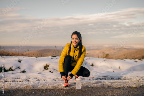 Fotografía  Happy sporty woman crouching and tying shoelace on the road in