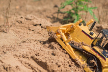 Small Plastic Toy Digger Working On Sand Quarry, Construction Concept