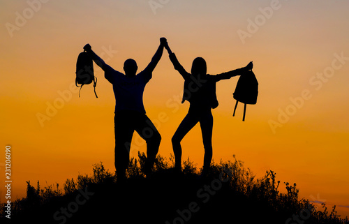 Photo  two silhouettes of people with backpacks on top of the mountain against the evening sky