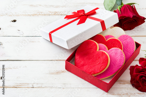 Heart-shaped cookies in gift box decorated with roses for Valentine's Day on white wooden table Canvas Print
