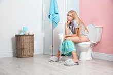 Woman With Paper Roll Sitting On Toilet Bowl In Bathroom
