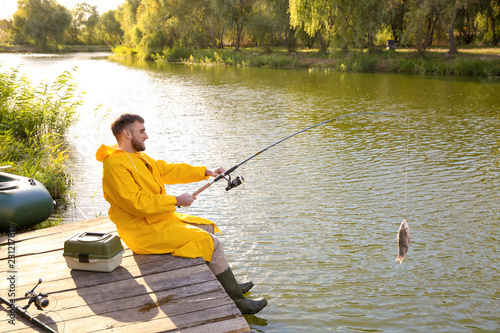 Photo Man with rod fishing on wooden pier at riverside