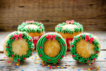 Fototapeta Christmas wreath cupcakes - beautiful and delicious homemade cupcakes decorated with green cream and candy sprinkles, Christmas and New Year dessert