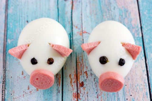 Food art idea for kids - funny edible piggies from boiled eggs, sausage and black pepper