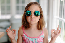 Beautiful Young Girl With Sunglasses Making A Hand Sign