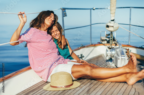 Smiling mother and daughter enjoying on sailboat