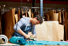 Male Worker Cutting Fabric With Rotary Cutter In Sofa Workshop