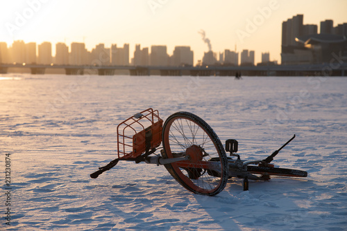Fotografie, Obraz  Deserted bike in a icy Hun river in Shenyang, China, whit beautiful sunset above