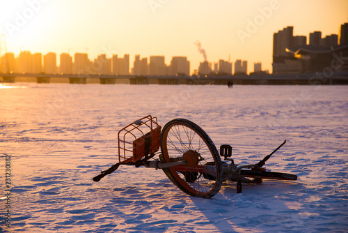 Fotografie, Obraz  Deserted bike at big icy river in Shenyang, China, while beautiful sunset above