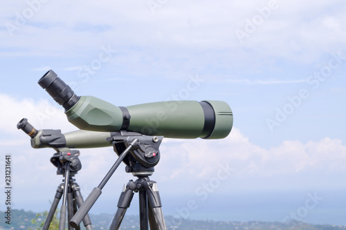 Fotografía  Green spotting scope or monocular at mountain top against the background of a mountain landscape in summer day