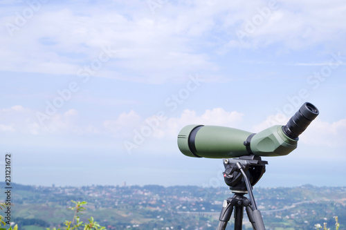 Fotomural  Green spotting scope or monocular at mountain top against the background of a mountain landscape in summer day
