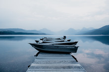 Boats Docked On A Pier Surrounded By A River And Mountains