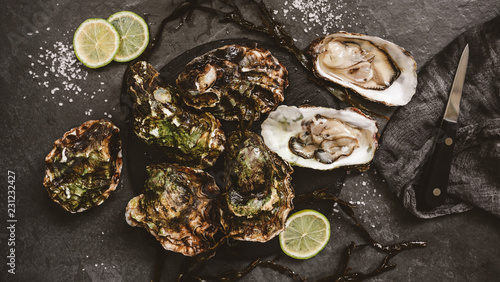 Fresh opened oysters with lemon, spices, salt, a knife and seaweed on slate stone background. Seafood, Shellfish, toning, top view