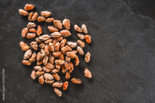 Frozen peeled mussels on slate stone background. Seafood, top view, flat lay, copy space