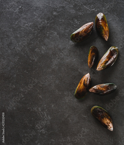 Fresh raw mussels on slate stone background. Seafood, top view, flat lay, copy space