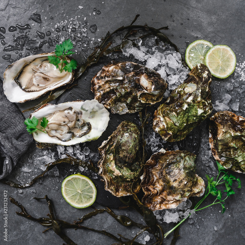 Fresh opened oysters with lemon, spices, salt, a knife and seaweed on slate stone background. Seafood, Shellfish, top view